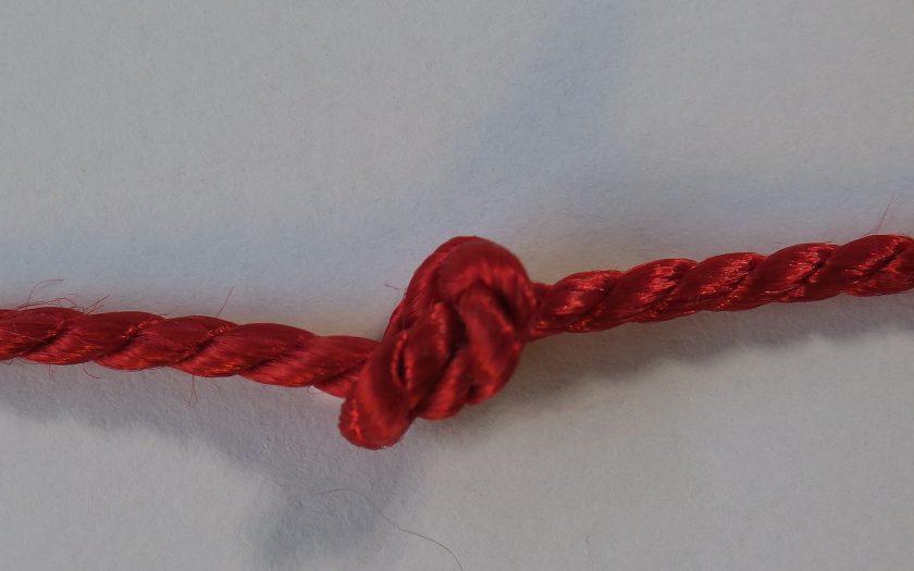 ein roter Faden mit Knoten