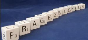 Buchstabenwürfel auf blauem Hintergrund formen das Wort Fragezeichen.